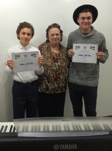 Carolyn Uhri presents Aidan Caplan and Cameron Carr their Certificates of Merit