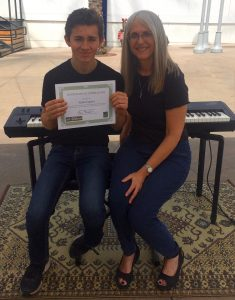 Pastimes for a Lifetime piano student Aidan C receives a certificate of merit for his performance at the Downtown Burbank Arts Festival